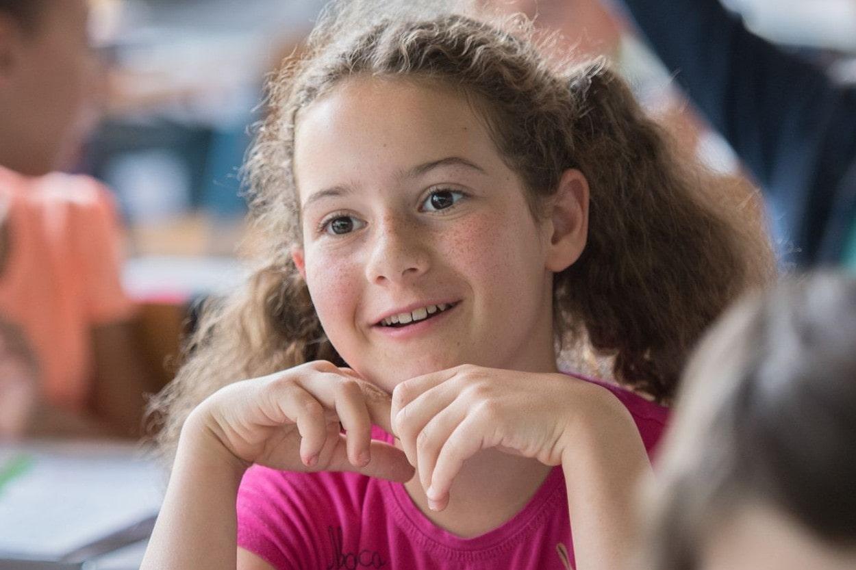 Jeune fille souriante et attentive lors d'un atelier de philo avec les enfants