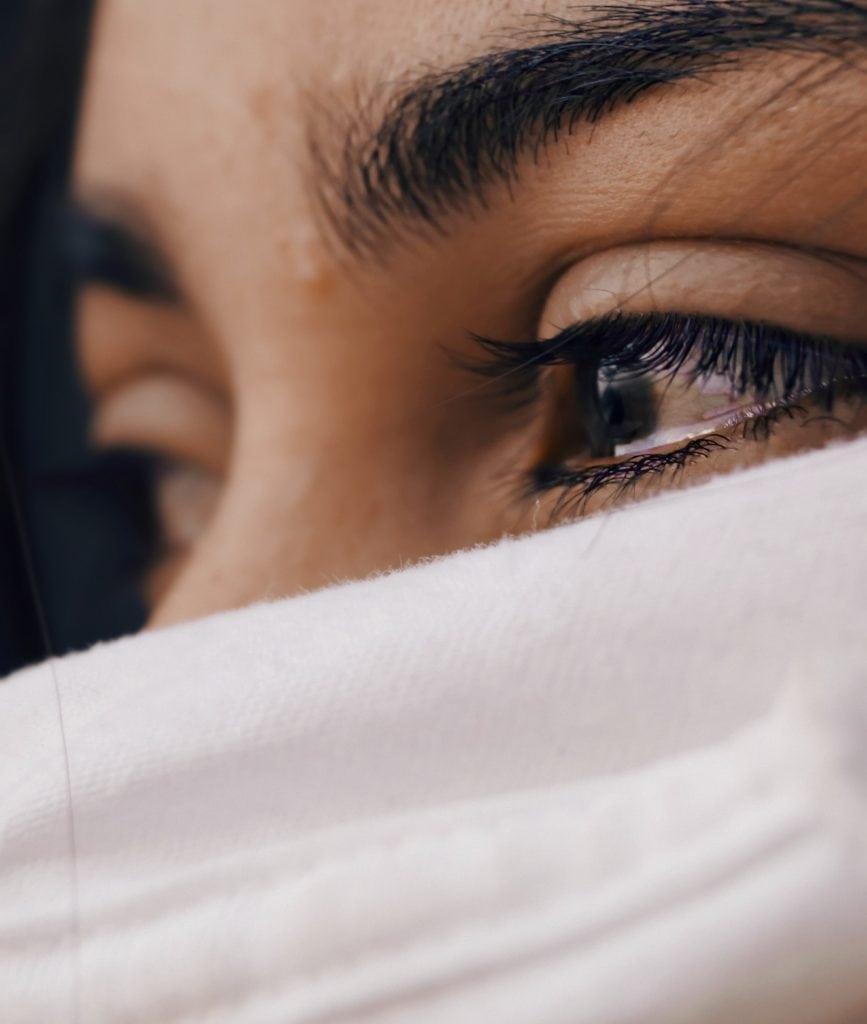 Femme aux yeux rougis par la fatigue portant un masque.