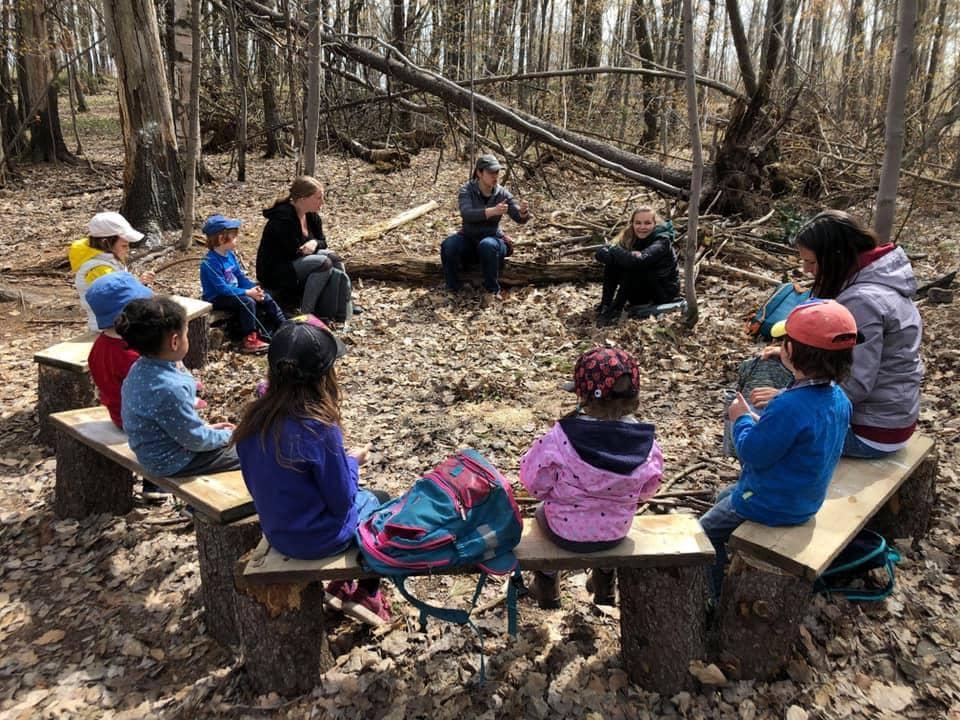 Cercle d'enfants en nature pendant un séance de contes et légendes.