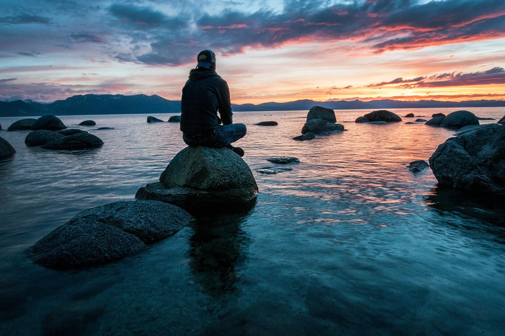 Homme qui médite près de l'eau pour illustrer la une de cet article qui explique comment méditer.