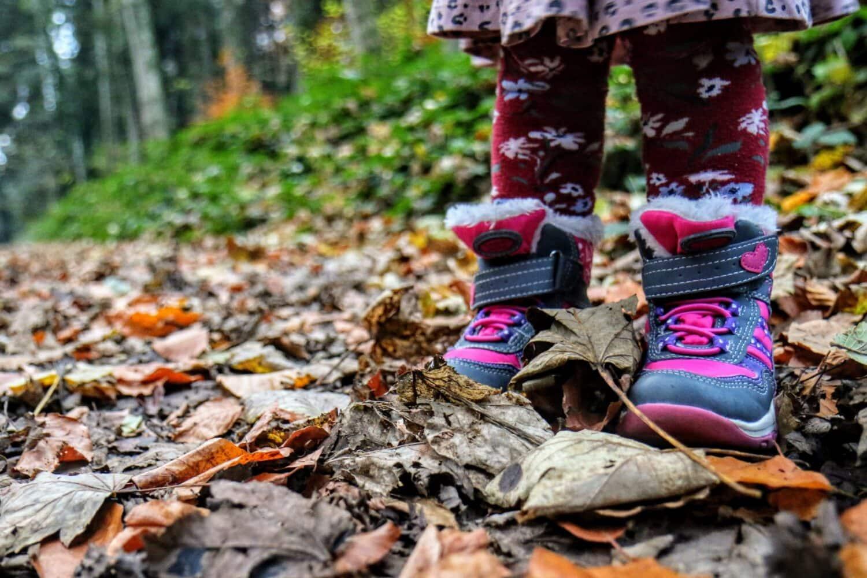 Enfants en nature les pieds dans les feuilles d'automne.