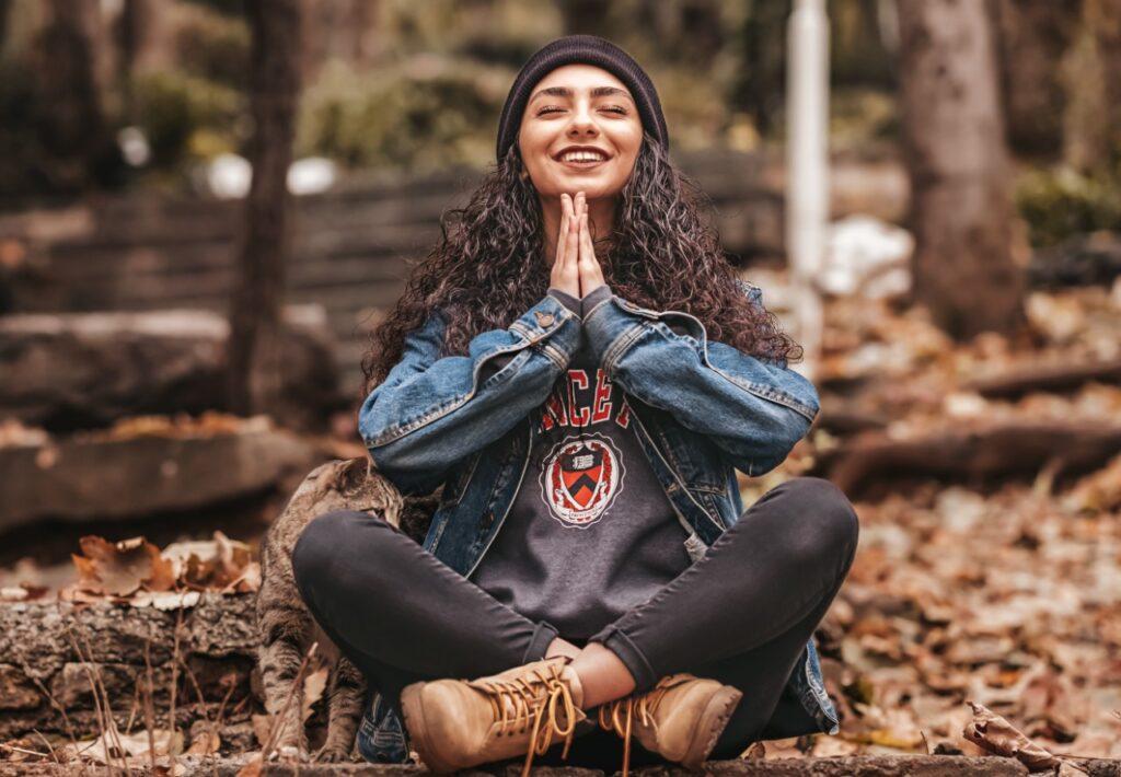 Femme qui médite en nature pour illustrer le fait qu'il est possible de méditer dehors dans cet article sur comment méditer.