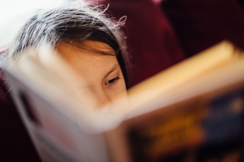 Enfant qui lit, seule, pour illustrer la une de cet article traitant de la relation parent-enfant.
