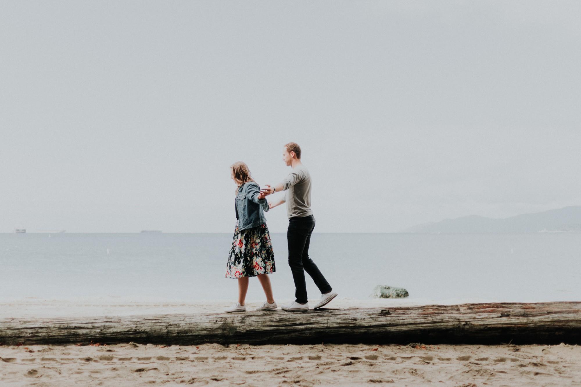 Un homme et une femme en équilibre sur un tronc de bois face à la mer.