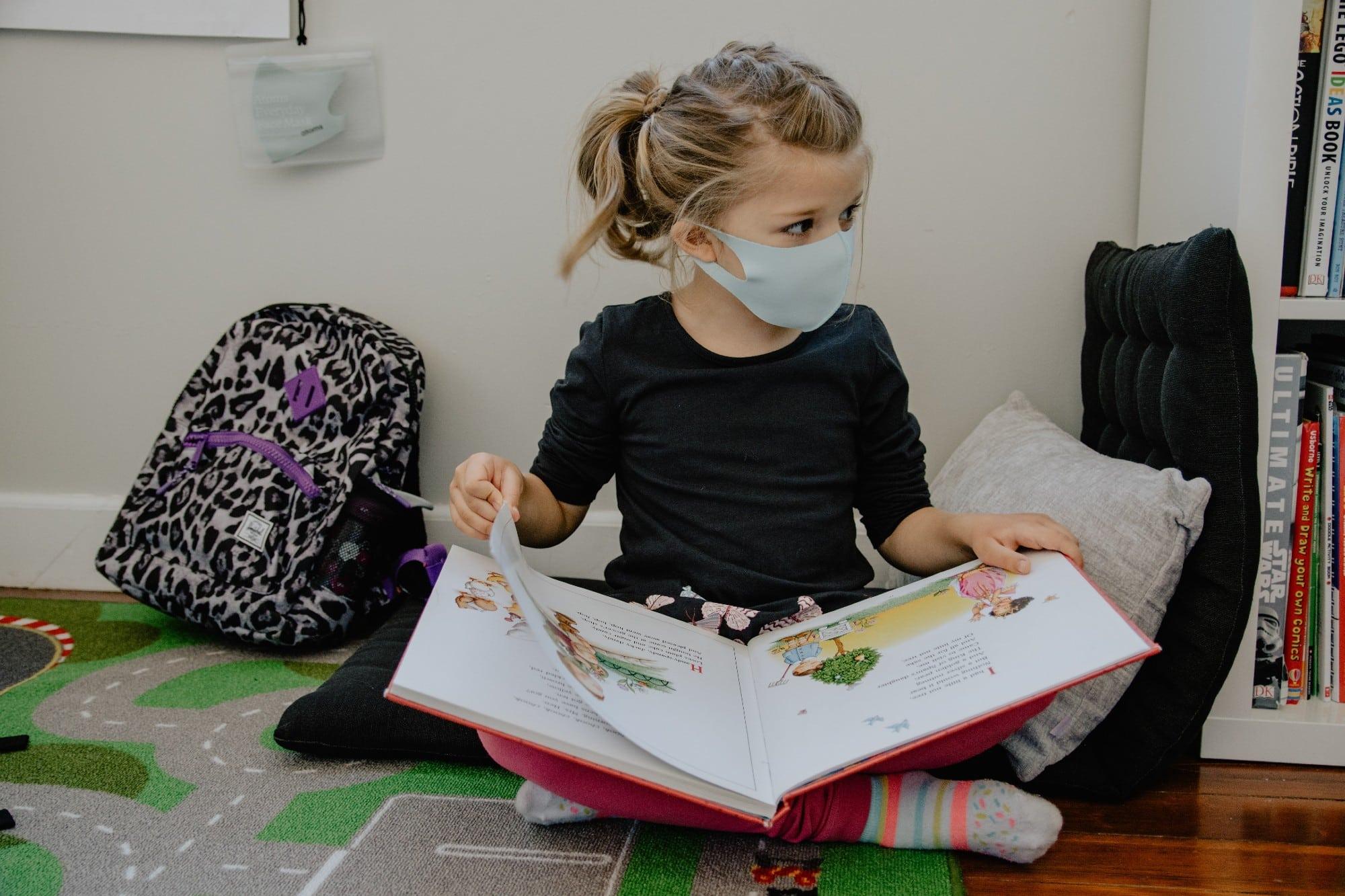 enfant qui lit un livre à l'école avec son masque