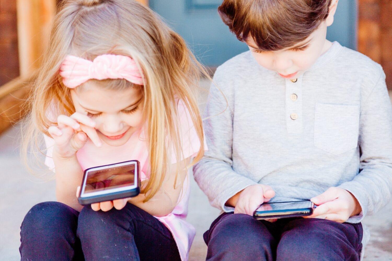 Image à la une de cet article au sujet du temps passé par les enfants devant les écrans: deux jeunes jouent sur leur cellulaire.