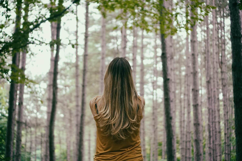 Image d'une femme en forêt pour la une de cet article portant sur les bienfaits de la nature.