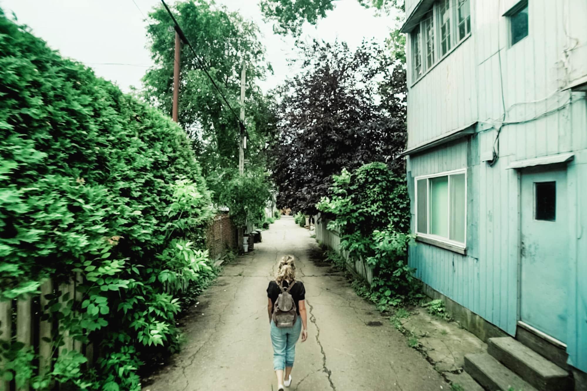 Joanie Lacroix marche dans une ruelle. La fondatrice de Pastel Fluo nous raconte sa renaissance suite au deuils dans cette entrevue en 3 questions.