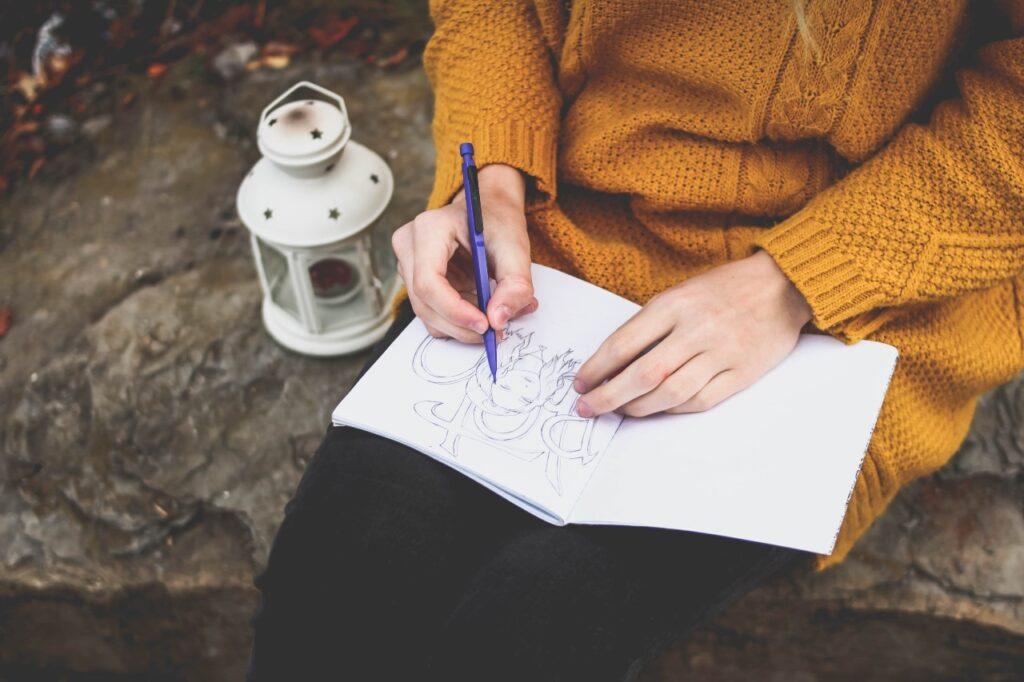 Femme en pleine écriture de son journal créatif