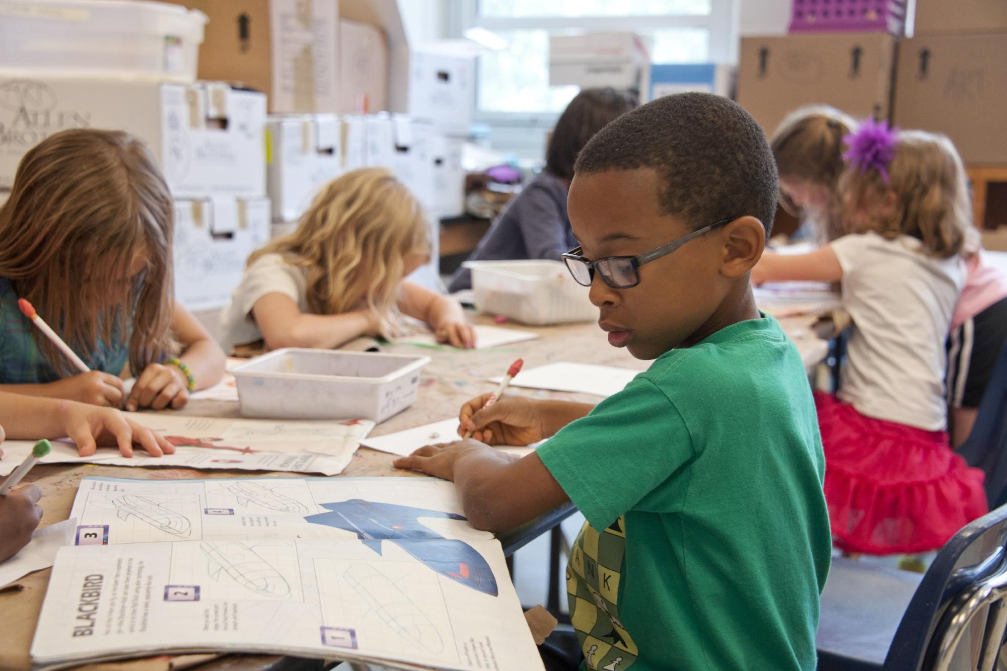 Jeune garçon d'âge primaire et sa classe en plein cours d'art